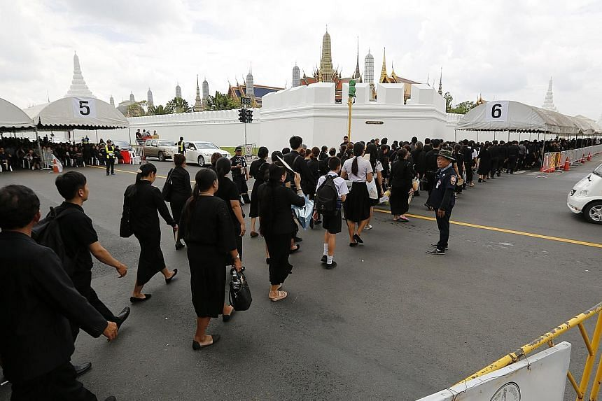 Thousands of Thais, dressed in mourning colours, lining up to pay their last respects to King Bhumibol Adulyadej outside the Grand Palace in Bangkok yesterday. The royal cremation will take place on Oct 26.