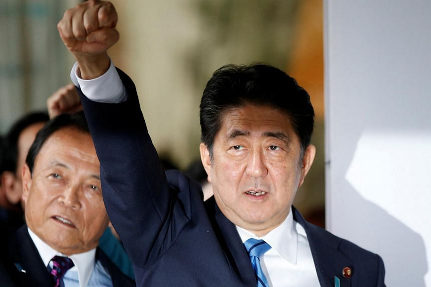 Japan's Prime Minister Shinzo Abe and his party's lawmakers, including Taro Aso (left), at their party headquarters in Tokyo, Japan on Sept 28, 2017.