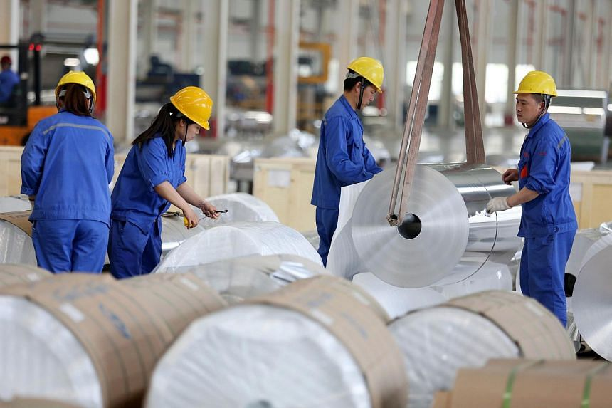 Chinese workers packaging aluminium tapes at an aluminium production plant in Huaibei, east China's Anhui province, on May 20, 2017.