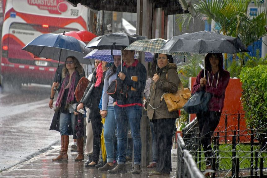 Locals wait at a bus stop during a downpour caused by tropical storm Nate in Cartago, 25km east of San Jose, Oct 5, 2017.