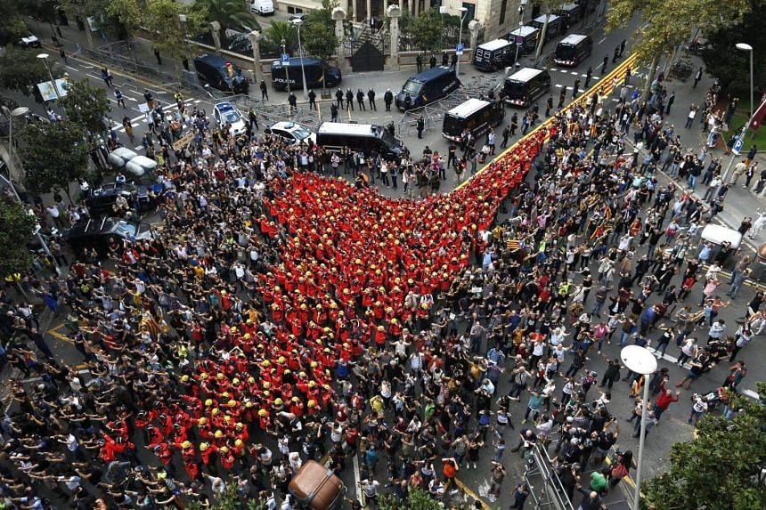 Firefighters join a demonstration at the Catalan Government's headquarters in Barcelona, on Oct 3, 2017.