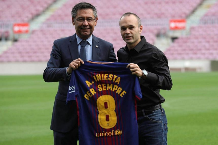 FC Barcelona captain Andres Iniesta holds up a jersey with FC Barcelona's President Josep Maria Bartomeu in Barcelona, Spain on Oct 6, 2017.