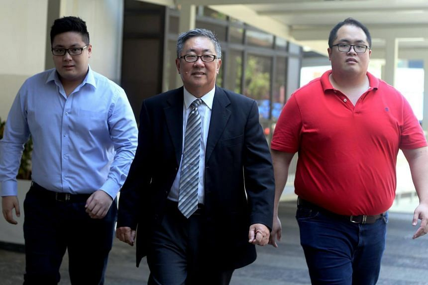 Senior Counsel Tan Chee Meng (centre) arriving at the State Courts on Friday (Oct 6) with his younger son Isaac Tan Yang En (left) and his elder son Jonathan Tan Huai En.