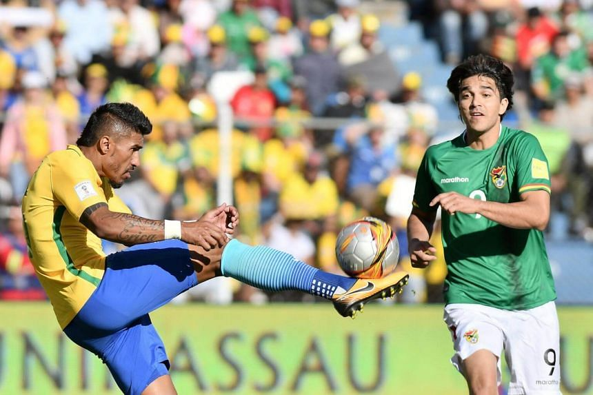 Bolivian Marcelo Martins (right) vies for the ball with Brazilian Paulinho (left) during the 2018 FIFA World Cup qualifying soccer match at Hernando Siles Stadium in La Paz, Bolivia on Oct 5, 2017.