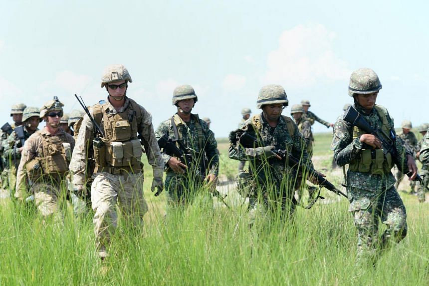 Philippine marines (in green) and their US counterparts (in light brown) after simulating an assault during the annual Philippines-US amphibious landing exercise at the navy base facing the South China Sea in San Antonio, on Oct 9, 2015.