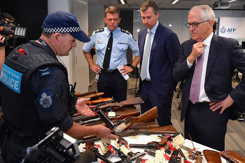 Australian Prime Minister Malcolm Turnbull looks at firearms with Australian Federal Police Commissioner Andrew Colvin and Australian Justice Minister Michael Keenan in Sydney, Australia, on Oct 6, 2017.