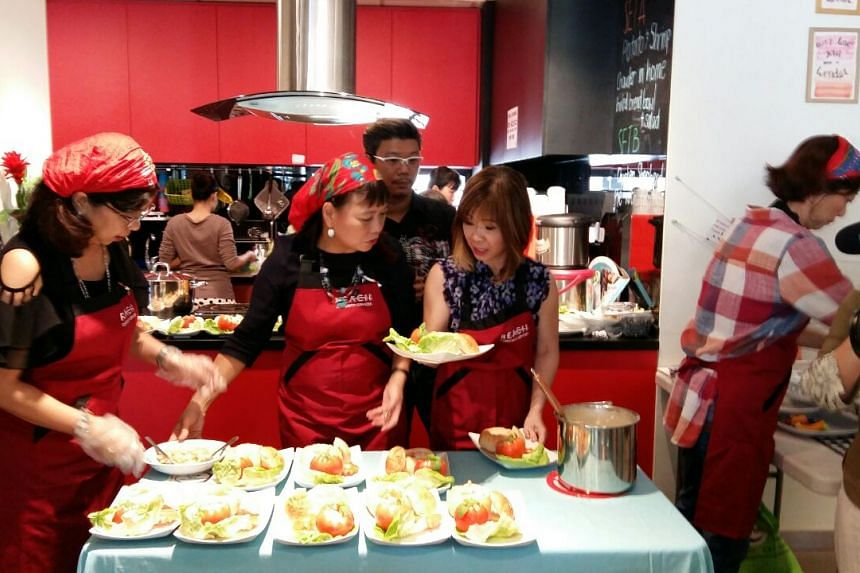 Dr Amy Khor, Senior Minister of State for Environment and Water Resources, and Health, serving patrons at the Reach community cafe officially launched on Friday (Oct 6).