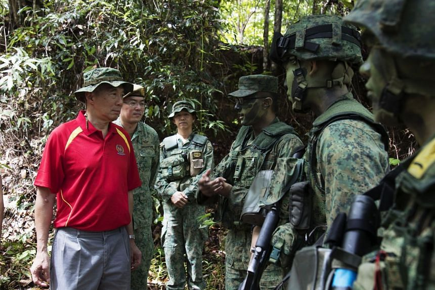 Prime Minister Lee Hsien Loong and Major-General Melvyn Ong (second from left) interacting with the national servicemen who had just taken part in the jungle and survival training.