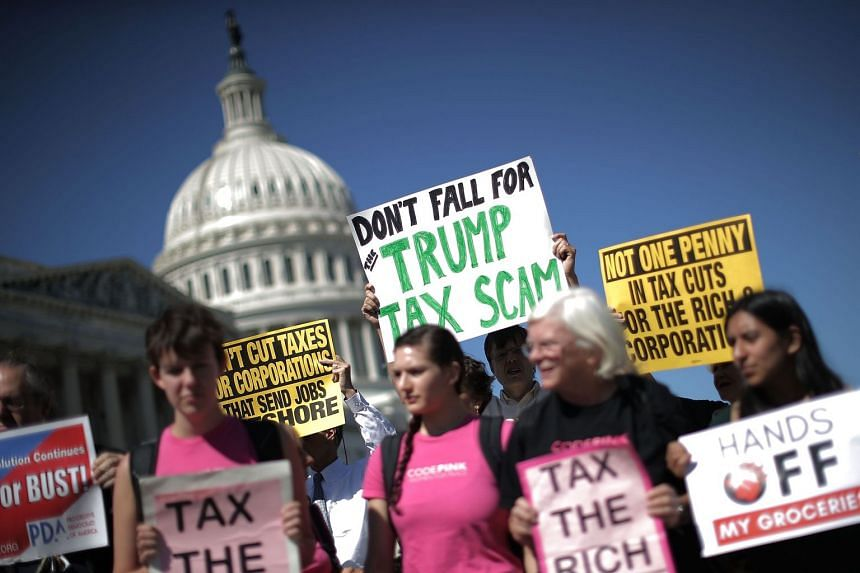Activitsts voice their opposition to the proposed Republican tax cut plan outside the US Capitol, Oct 4, 2017.