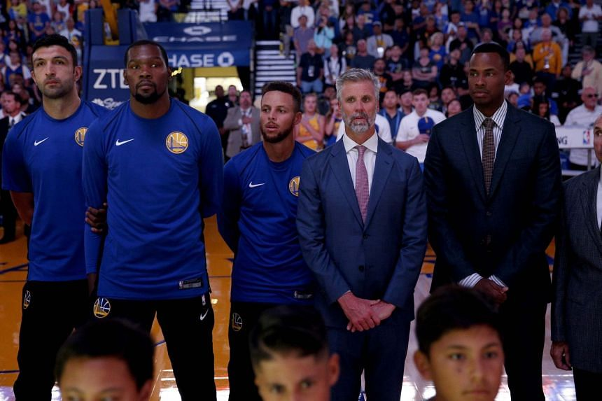 Golden State Warriors guard Stephen Curry (third from left) next to forward Kevin Durant during the US national anthem before the start of the Sept 30 game against the Denver Nuggets at Oracle Arena.
