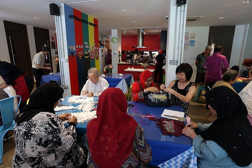 Above: Volunteer Mary Sim, 68, serving Madam Tan Keok, 84, at the newly launched Reach Community Cafe in Bukit Batok West Avenue 4. Left: Seniors making pillows out of old T-shirts after having a meal at the cafe. The cafe's aim is to draw older folk
