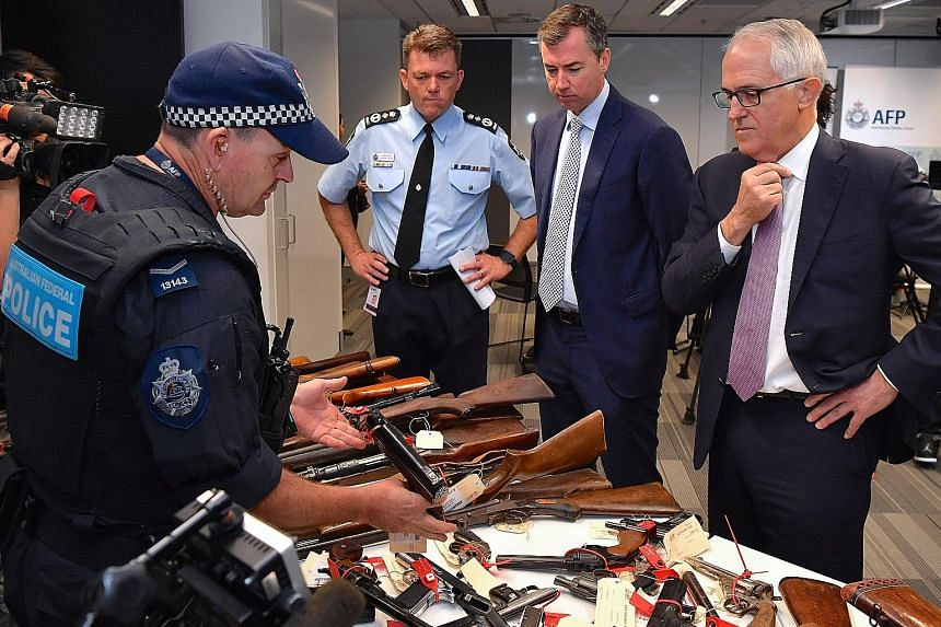 (From right) Prime Minister Malcolm Turnbull, Justice Minister Michael Keenan and Australian Federal Police Commissioner Andrew Colvin yesterday with some of the guns surrendered.