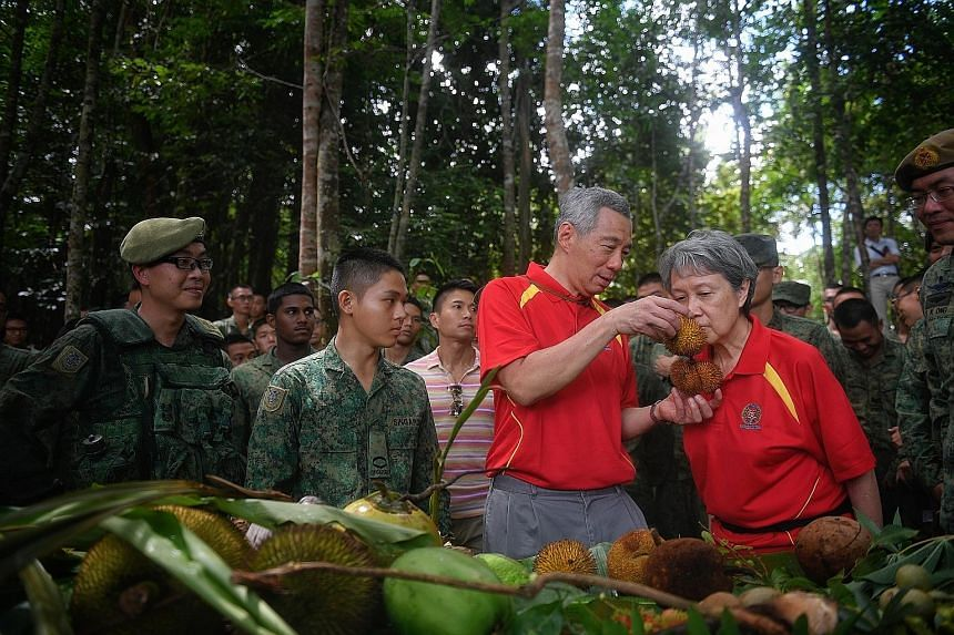Prime Minister Lee Hsien Loong and Mrs Lee being shown various fruits that soldiers learn to survive on during the jungle training at Temburong in Brunei. Accompanying them was Chief of Army Melvyn Ong (right).