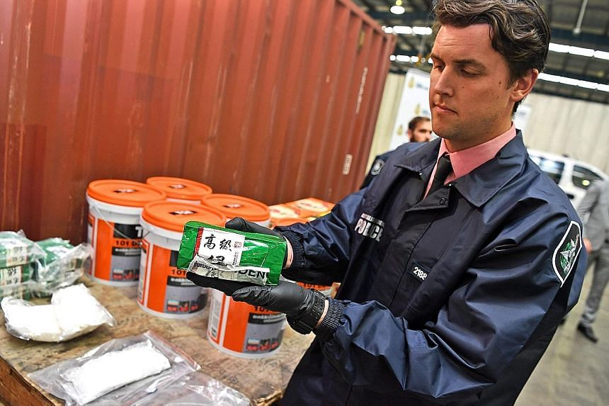 A police officer with a packet of liquid ephedrine at a press conference in Sydney yesterday. The 3.9-tonne haul of liquid ephedrine, concealed in a shipment of green-tea bottles from Thailand, is the biggest bust of the illegal substance in Australi