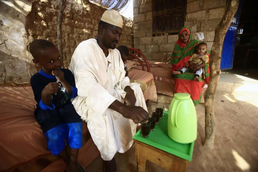 Sudanese engineer Ahmed Abdallah (left) with his wife Shahinda Adel and their children in their home on the outskirts of the Sudanese capital's twin city of Omdurman on Oct 2, 2017.