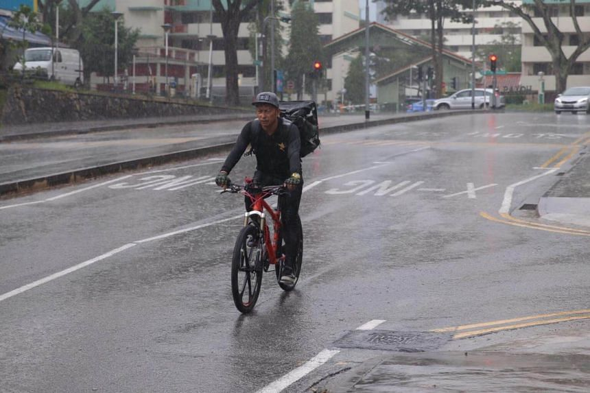 A delivery rider on his rounds at Toa Payoh despite the heavy rain on Oct 7, 2017.