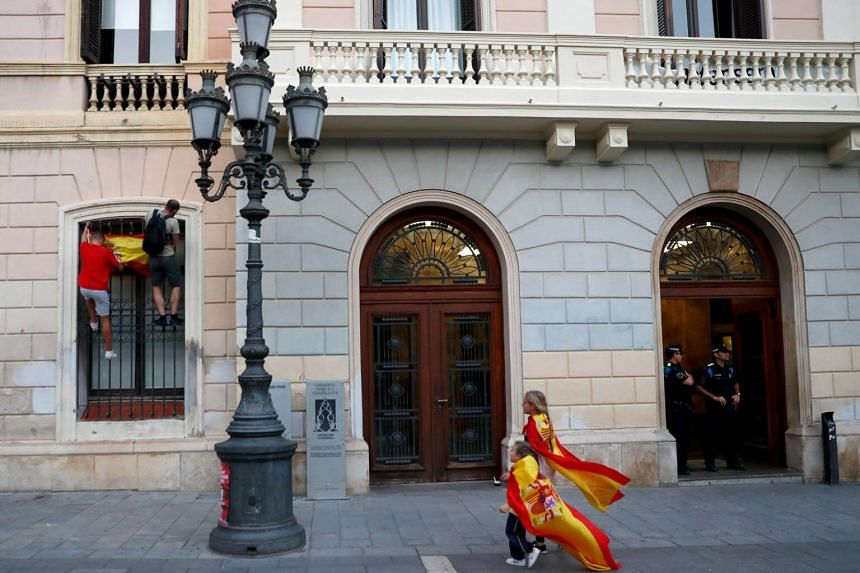 Men climb a window of the municipal government building to attach Spain's flag to the railings during a demonstration by pro-union supporters in a square in Sabadell, Calatonia, Spain on Oct 6, 2017.