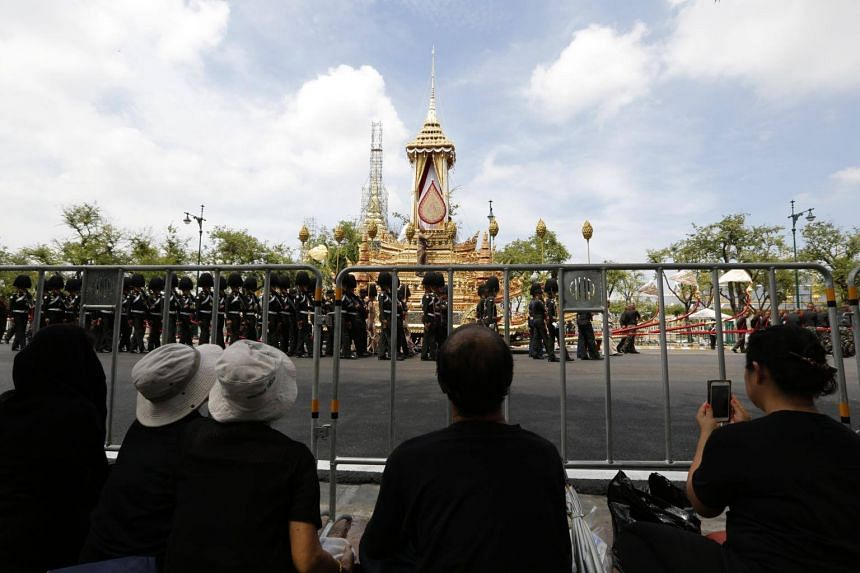 Thais watch a training exercise to pull a royal funeral chariot vehicle, which will be used in the procession for the royal funeral pyre of late Thai King Bhumibol Adulyadej's cremation ceremony, at Sanam Luang near the Grand Palace in Bangkok, Thail