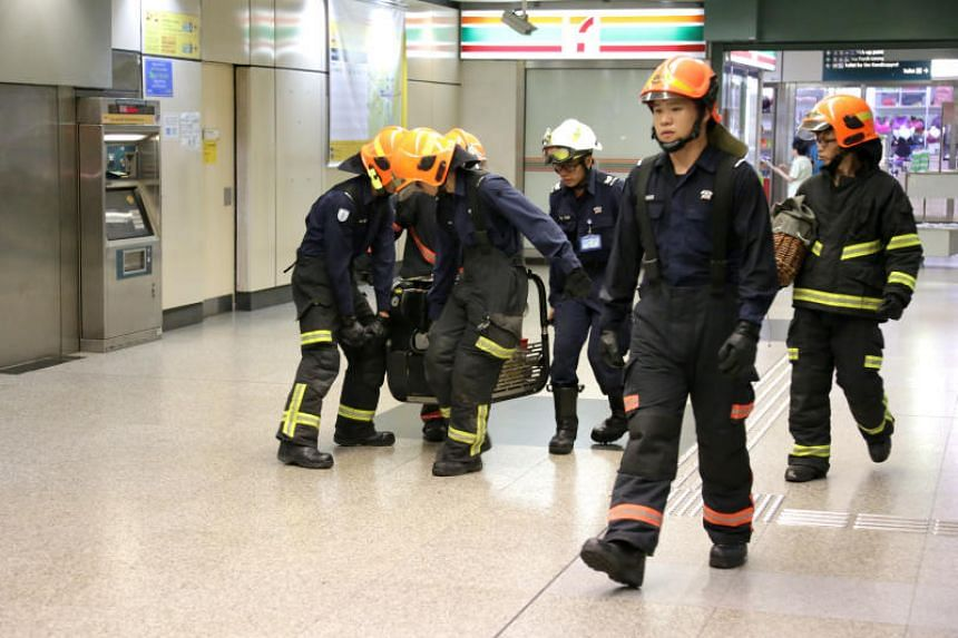 SCDF officers carrying equipment into Braddell MRT station on Saturday. Train services on the North South Line were affected after water entered the tunnel from Bishan to Braddell stations amid a downpour.
