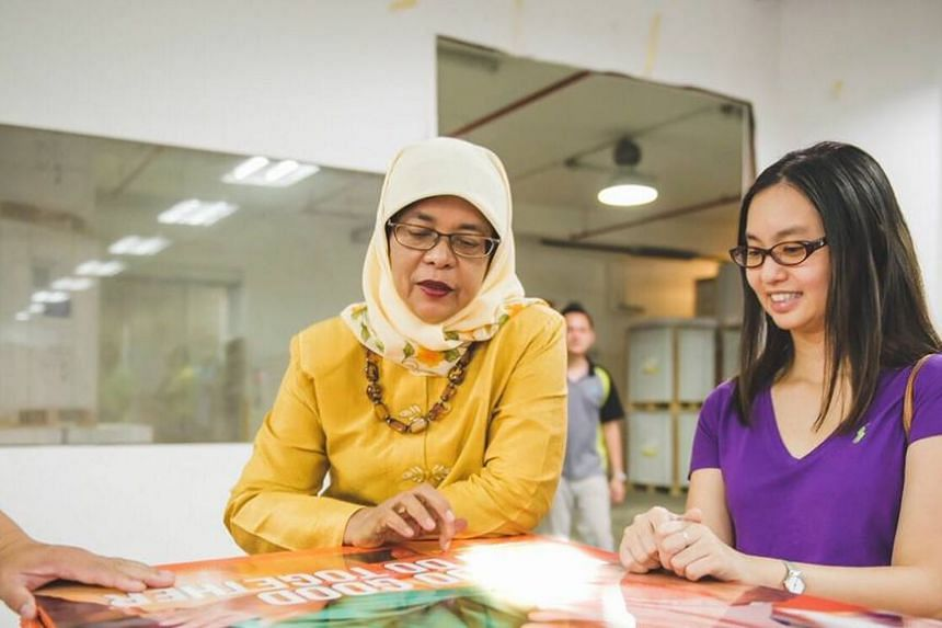 President Halimah Yacob looking at a poster for her presidential campaign. All unused donations will be returned to donors, a statement from her campaign team said today (Oct 7).