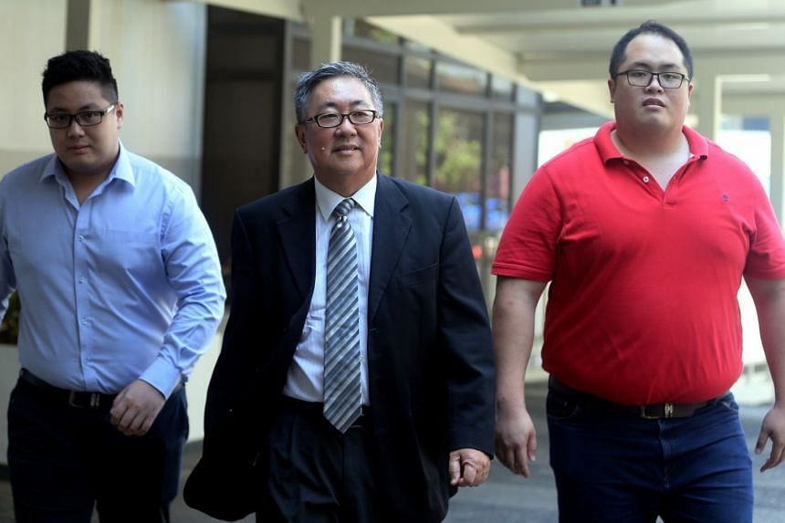 Isaac Tan Yang En (left) with his father, Senior Counsel Tan Chee Meng, and brother Jonathan Tan Huai En yesterday. Isaac Tan pleaded guilty to one count of remaining outside Singapore without a valid exit permit. His brother surrendered himself to t