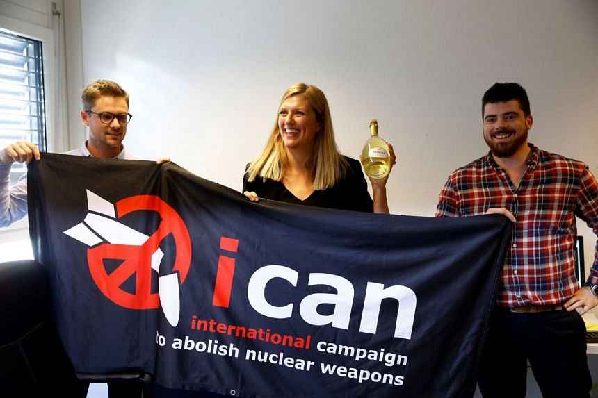Ms Beatrice Fihn, executive director of the International Campaign to Abolish Nuclear Weapons (Ican), celebrating with a bottle of champagne from her husband Will Fihm Ramsay (right), and Ican coordinator Daniel Hogsta, after the group won the Nobel