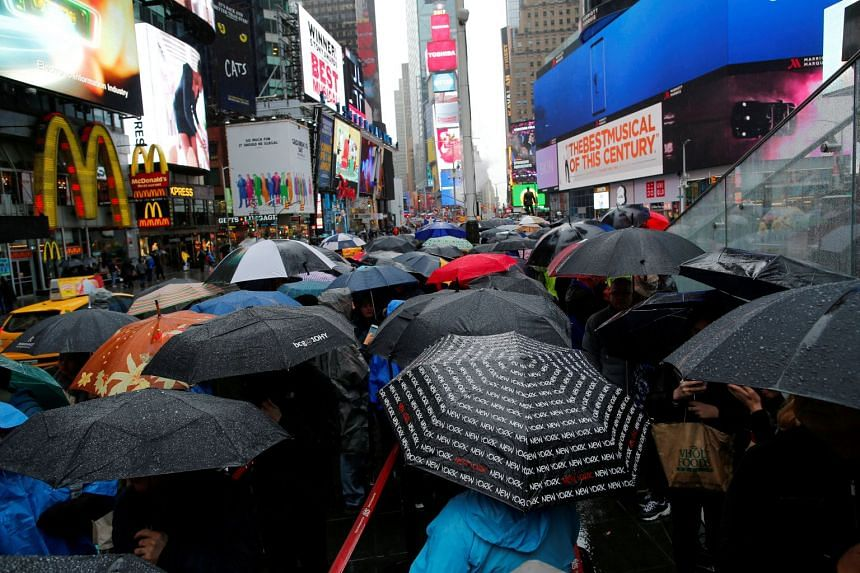 People walk in the rain in Times Square in New York, US, on May 13, 2017.