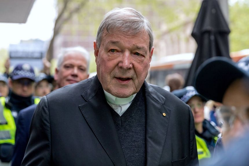 George Pell is surrounded by Australian police as he leaves a Melbourne court, Oct 6, 2017.