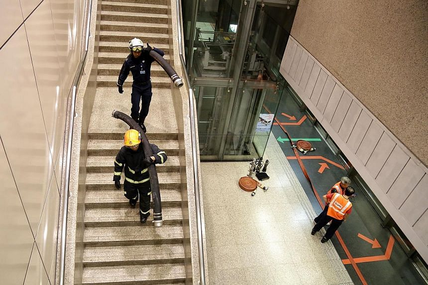 SCDF staff carrying equipment into Braddell station during yesterday's service disruption.