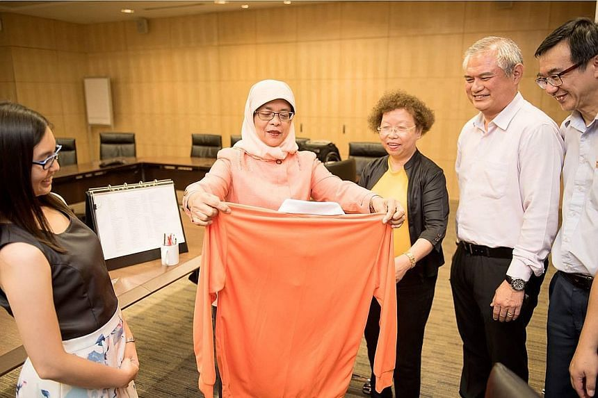 Madam Halimah Yacob examining a campaign T-shirt with some members of her team before Nomination Day. Campaign expenses by a presidential candidate are subject to a legal limit - which was $754,982.40 this year.