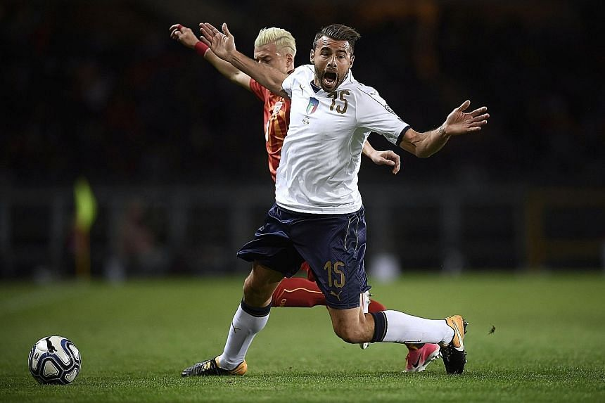 Italy defender Andrea Barzagli being tackled by Macedonia defender Ezgjan Alioski on Friday in Turin. His exit at half-time added to the Azzurri's lengthening injury list.