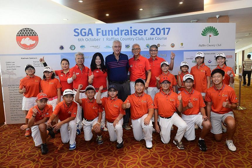 Emeritus Senior Minister Goh Chok Tong (in blue) with Singapore Golf Association (SGA) board members and young golfers from the national junior squad during the SGA's annual fund-raiser at Raffles Country Club on Friday. He was the guest of honour fo
