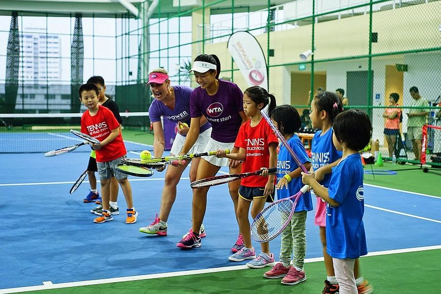 Tennis player Tammy Tan (white visor), one of Singapore's eight WTA Future Stars representatives, guiding WTA Future Stars clinic participants yesterday with WTA Asia-Pacific vice-president and WTA Finals tournament director Melissa Pine (pink visor)