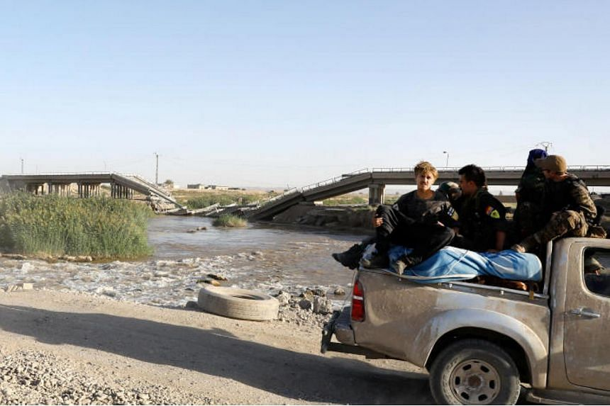 Members of Syrian Democratic Forces ride in a truck along a makeshift bridge overlooking a bridge destroyed by a U.S. air strike in the outskirts east of Raqqa, Syria on Oct 5, 2017.