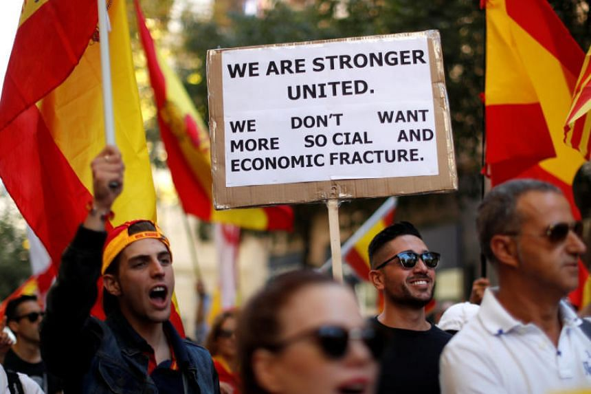 A man carries a placard in English during a pro-union demonstration organised by the Catalan Civil Society organisation in Barcelona, Spain, Oct 8, 2017.