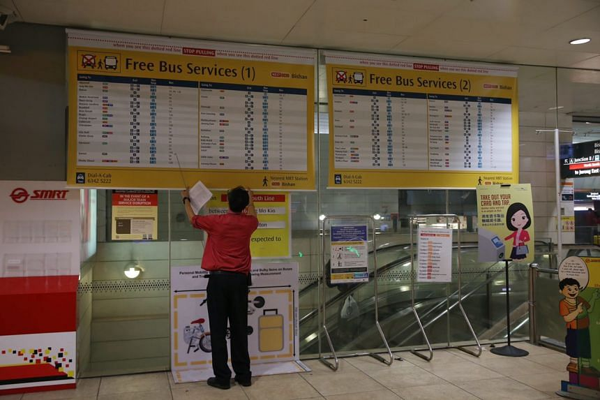 A member of the SMRT staff puts up signboards with information of free bus services.