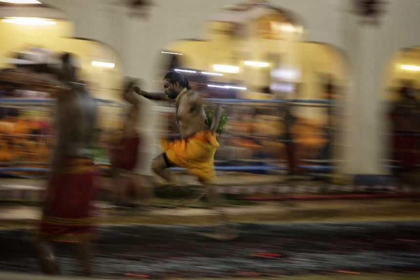 A devotee making his way across burning charcoal during the annual fire walking festival at Sri Mariamman Temple on Oct 8, 2017.
