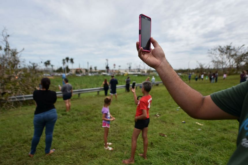 People try to get a cellphone signal in Dorado, 40km north of San Juan, Puerto Rico, on Sept 23, 2017.