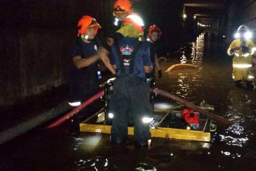 SCDF personnel working to remove water from the MRT tunnels between Bishan and Braddell stations. PHOTO: SCDF