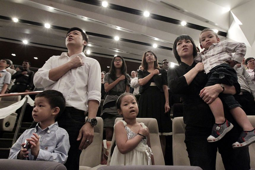 New Singapore citizens reciting the Pledge after receiving their citizenship certificates at a National Citizenship Ceremony.