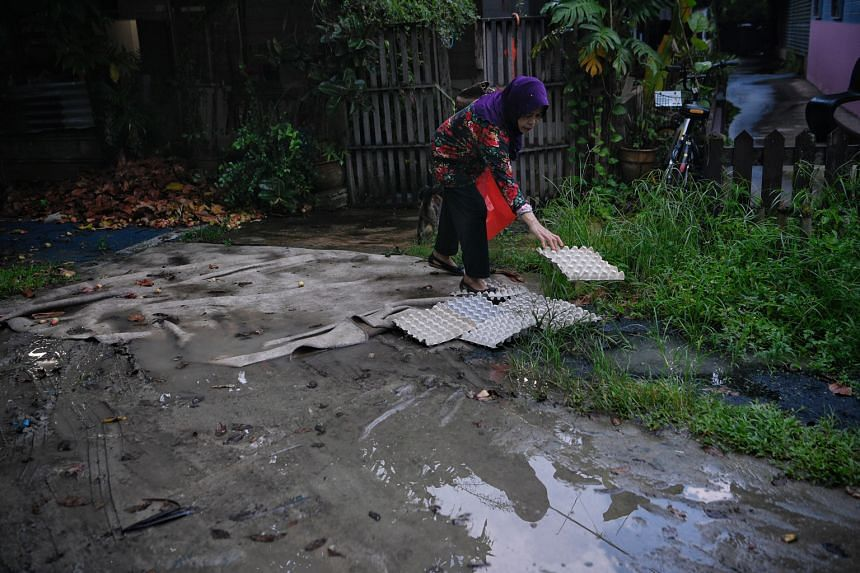 6PM: Above: Resident Annie Ridwan, 67, places egg cartons near her gate. Several puddles have formed due to the rain.