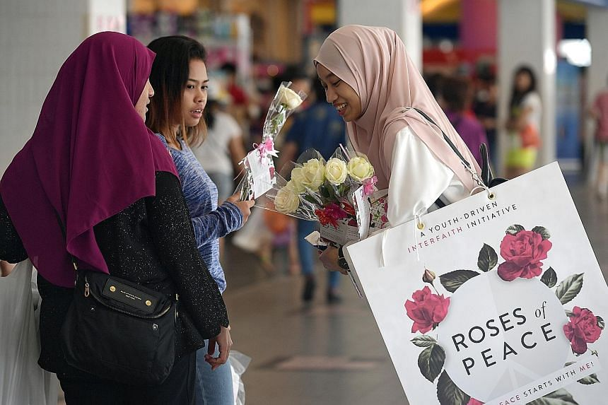 Singapore Management University student Nadya Batrisyia giving out roses at Tampines bus interchange yesterday as part of an initiative by group Roses of Peace, which promotes peaceful relations and religious harmony. About 230 young people distribut