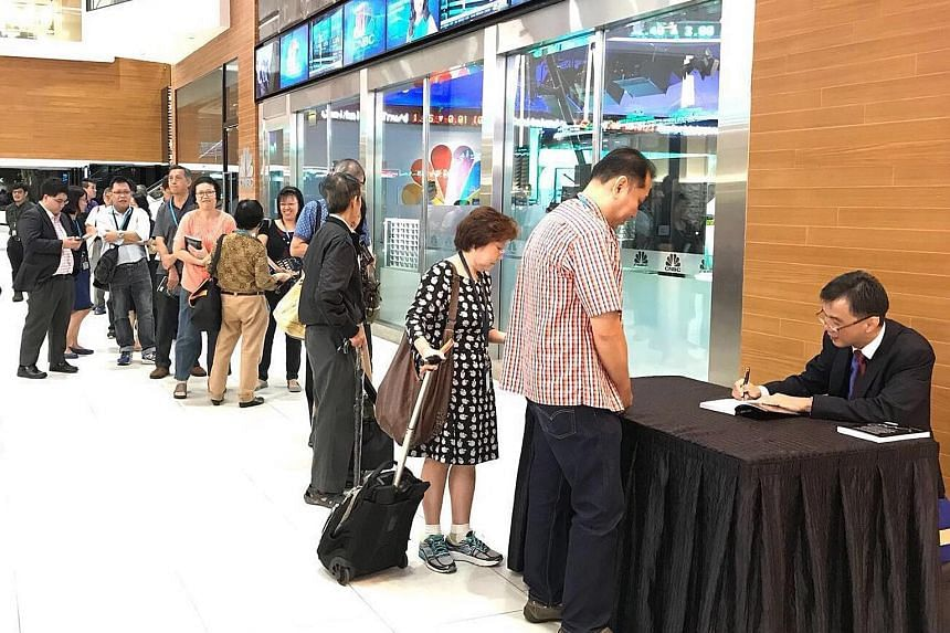 Mr Goh Eng Yeow signing copies of his latest book - Market Smart: How To Grow Your Wealth In An Uncertain World (above) - during its launch at the SGX Auditorium on Friday.