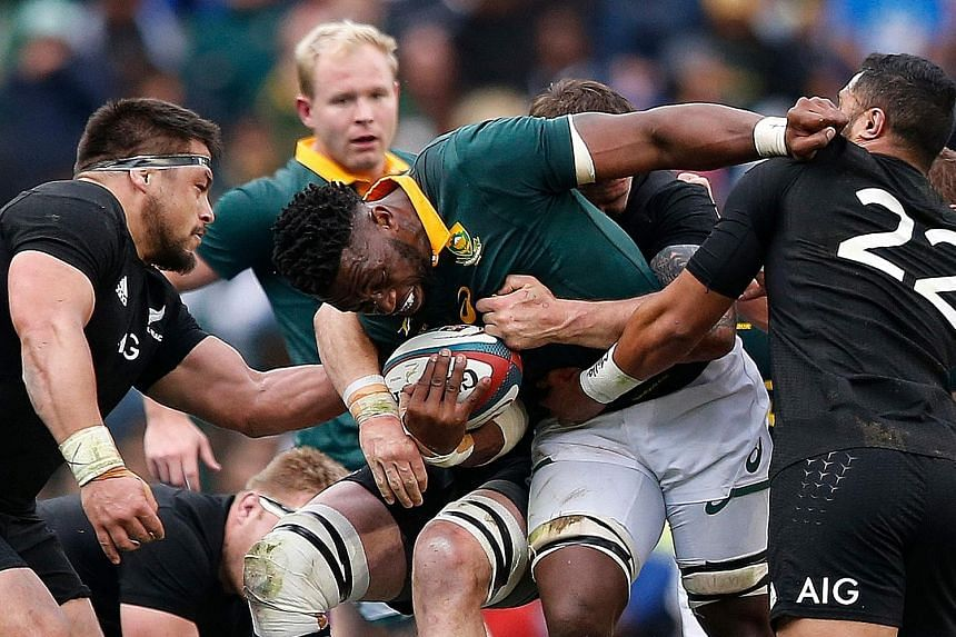 South African flanker Siya Kolisi being hauled down by All Blacks' fly-half Lima Sopoaga (No. 22) and his team-mates during their rugby Test on Saturday. The Springboks lost 25-24, but restored their pride after a 57-0 rout by the All Blacks last mon