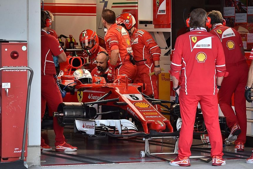 Ferrari's Sebastian Vettel waiting in the pits as mechanics work on his car. A spark-plug issue led to his early retirement and Hamilton now has a chance to win his fourth F1 title at the US Grand Prix.