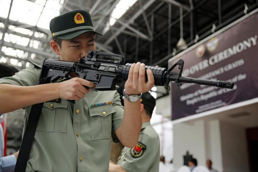 A Chinese military official inspecting a Chinese-made CQ-A5b assault rifles during a handover ceremony at a military camp in Quezon city, Philippines, on Oct 5, 2017.