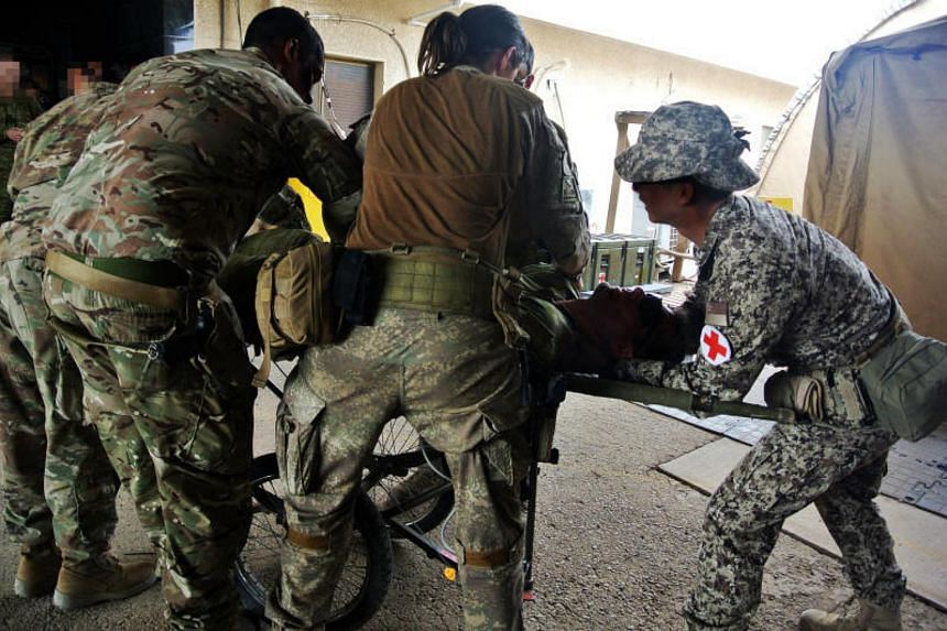 A Singapore Armed Forces medic practising a mass casualty drill with medics from Australia and New Zealand.