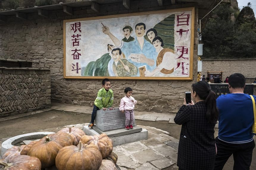 Parents photographing their children in front of the hostel where Chinese President Xi Jinping is said to have lived during his time in Liangjiahe, China, on Oct 6, 2017.