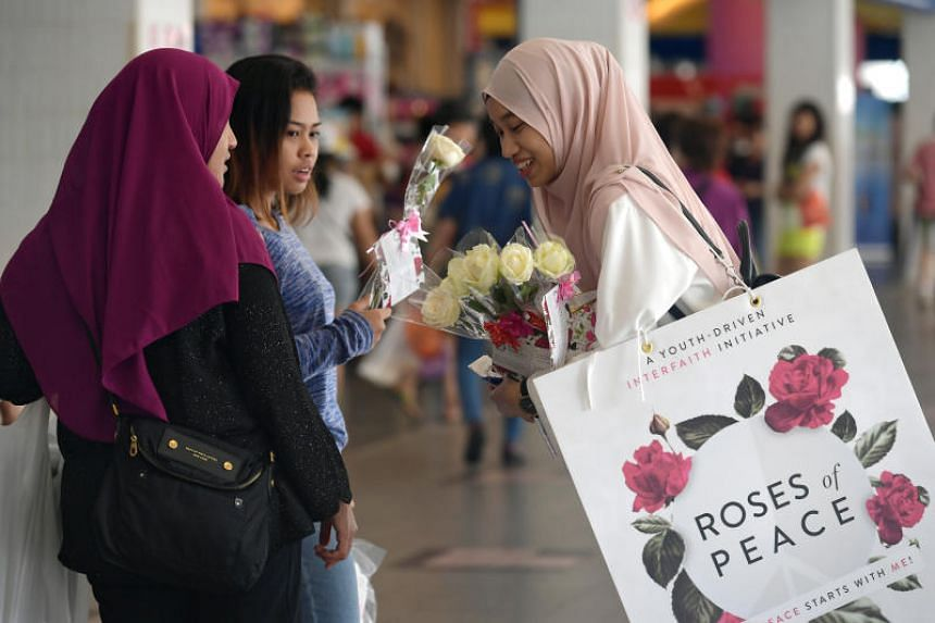Ng Sor Luan/SMU student Nadya Batrisyia (right) hands out roses at Tampines bus interchange as part of Roses of Peace 2017, #TogetherForPeace, organised by inter-faith group, Roses of Peace.