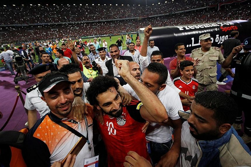 Above: Egypt winger Mohamed Salah (No. 10) celebrating the nation's entry into next year's World Cup Finals with his team-mates and fans at the Borg el-Arab Stadium on Sunday. The Pharaohs last took part in football's showpiece in Italy in 1990.